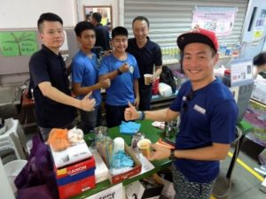 APSN Deputy CEO, Mr Gary Lim supporting students from APSN Katong School mending their drink stall with their instructors
